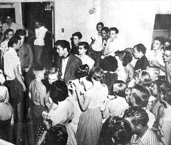 Buddy Holly (far right) watches Elvis