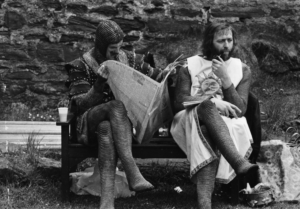 John Cleese reads a newspaper while Graham Chapman smokes a pipe on the set of Holy Grail