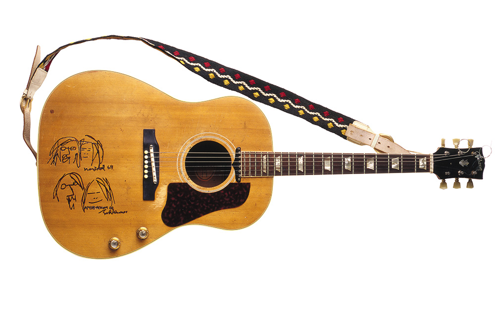 """John Lennon originally acquired this guitar in 1964 to replace an identical one that was stolen. He used it extensively throughout his career. It was prominently seen in the film Help! In 1967, the guitar was painted psychedelic blue and red by the Fool, the Dutch art cooperative that also painted Lennon's Rolls-Royce. In 1968, Lennon had the guitar's finish stripped to the natural wood finish. Lennon and Yoko Ono held two """"bed-ins"""" for peace in March and May of 1969, which Lennon commemorated by drawing caricatures of Yoko and himself on the guitar. It was during the second bed-in, held at the Queen Elizabeth Hotel in Montreal, that the single """"Give Peace a Chance"""" was recorded, using this guitar."""