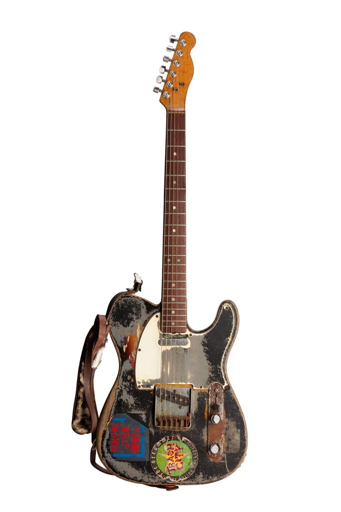 This guitar was Joe Strummer's principal instrument. He played it in the studio while with the Clash and throughout his solo career. After he acquired the guitar in the early 1970s, Strummer took the guitar to an auto-body shop, where he had it spray painted with gray primer.